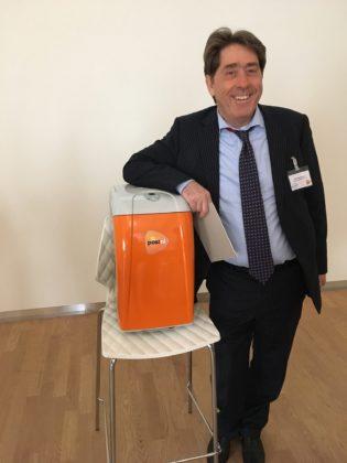Gerrit Mastenbroek, directeur PostNL pakketten, staat bij de nieuwste vinding van PostNL: een intelligent koelkastje die de temperatuur van medicijnen constant houdt.