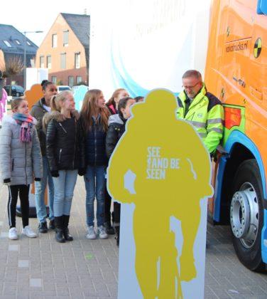 Instructeur Frank van der Sanden van Volvo Trucks buiten met een groepje kinderen.